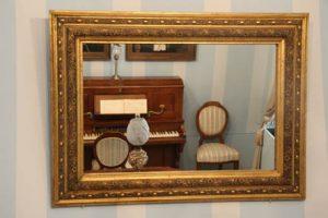 Zrcalo na zidu instalacije interijera građanskog salona u bidermajer stilu.